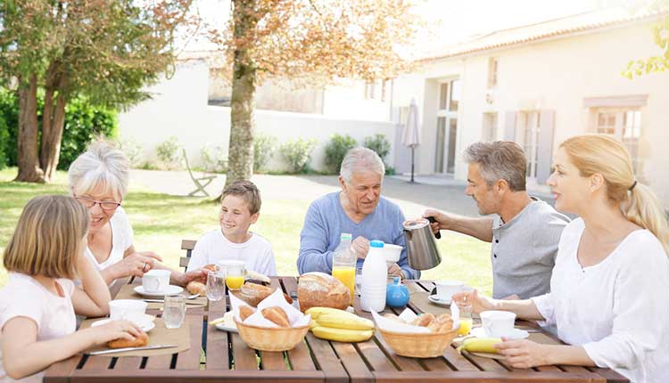 extended family eating together in the garden of a holiday home rental