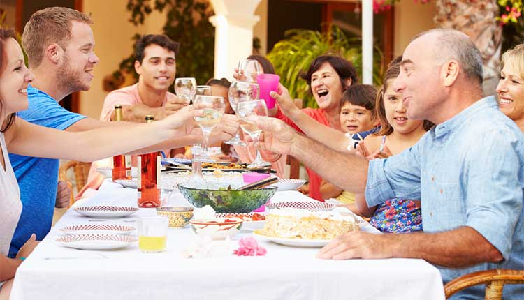 extended family eating together outside on holiday
