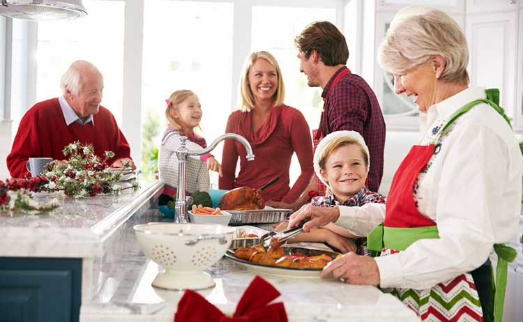 grandmother serving up christmas dinner in the kitchen with the extended family