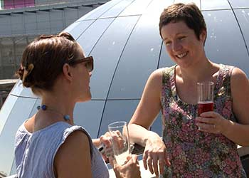 Two female SunLife employess laughing and drinking together on a company away day.