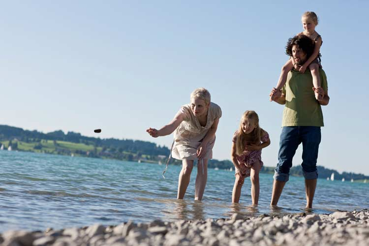 a family on a stoney beach paddling in the water skimming stones.