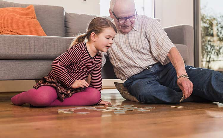 grandaughter and grandfather playing a game on the floor