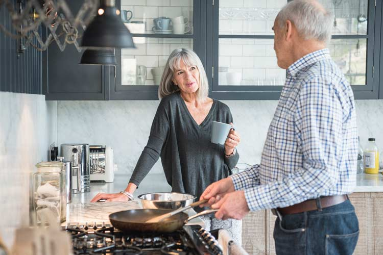 An over 50s couple talking in the kitchen while the gentleman uses a frying pan.