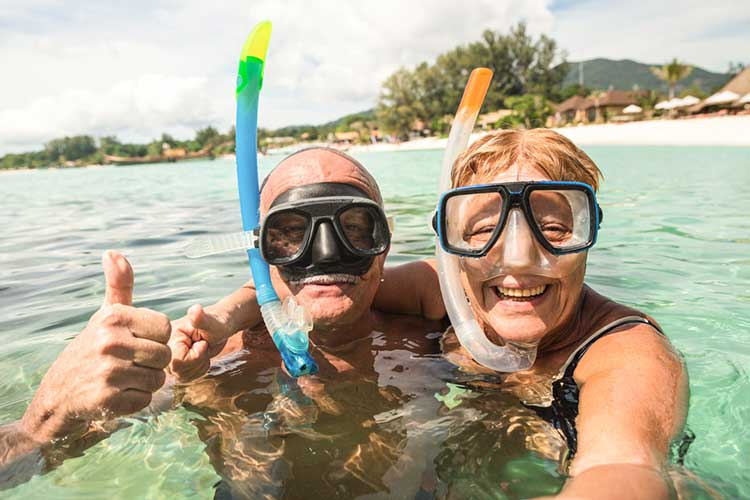An over 50s couple snorkeling on holiday.