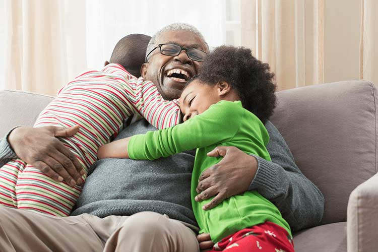A granfather hugging his two grandchildren on the sofa.
