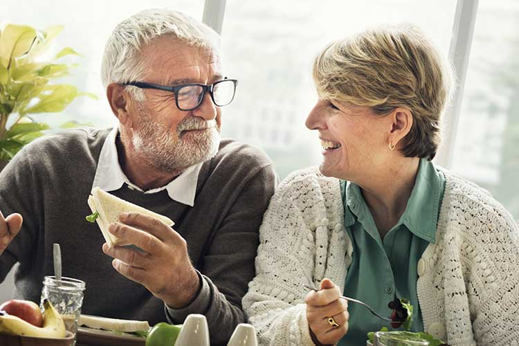An over 50s couple sat at a table eating lunch.