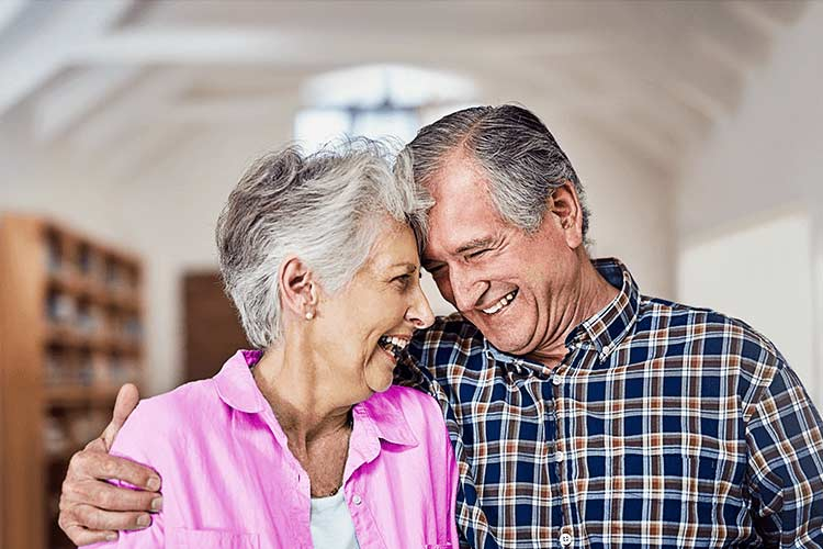 over 50 life insurance over 50s couple hugging and laughing