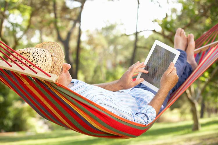 Elderly gentleman lying in a hammock looking at an ipad.