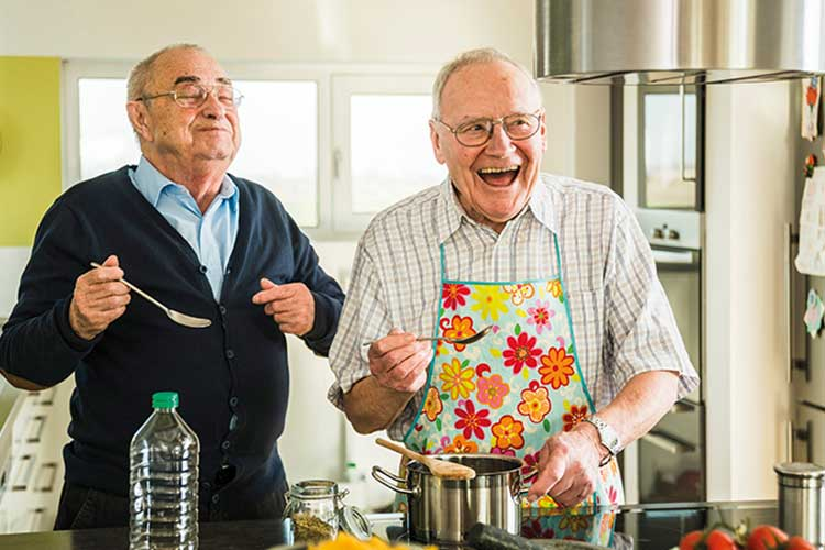 Two elderly men cooking and laughing.