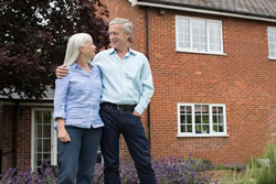 home insurance over 55s couple standing in front of their house.