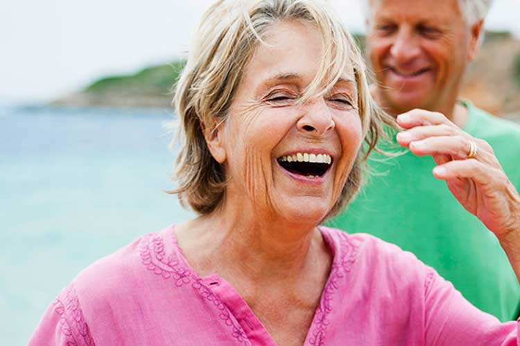 Over 50s couple laughing on the beach.