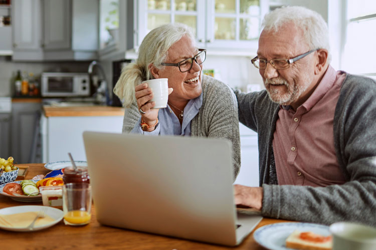 Over 55 couple sat in kitchen looking at laptop