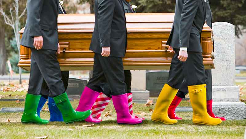 People carrying a coffin with colourful wellies on