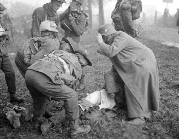 soldiers looking over a wounded soldier