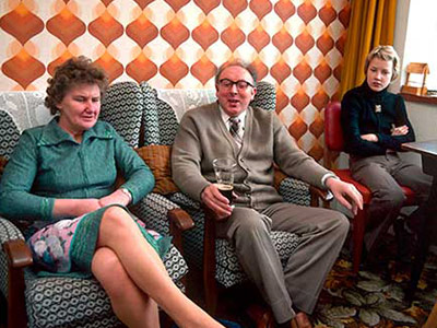 Three family members sitting in a 1970s lounge decorated in patterned wallpaper and carpet.