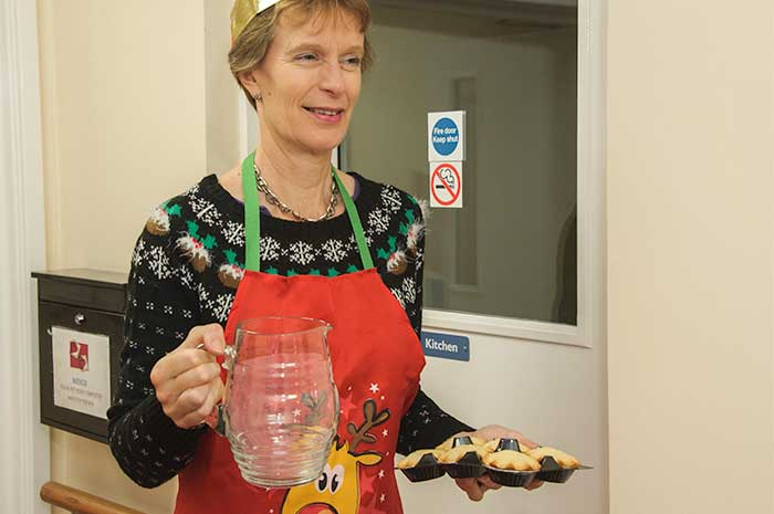 caroline billington helping at Christmas carrying mince pies and a jug of water