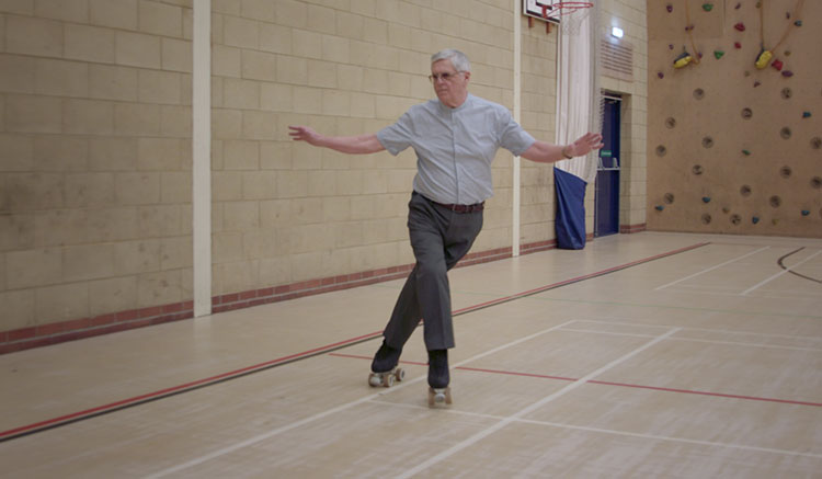 Clive roller skating in a hall