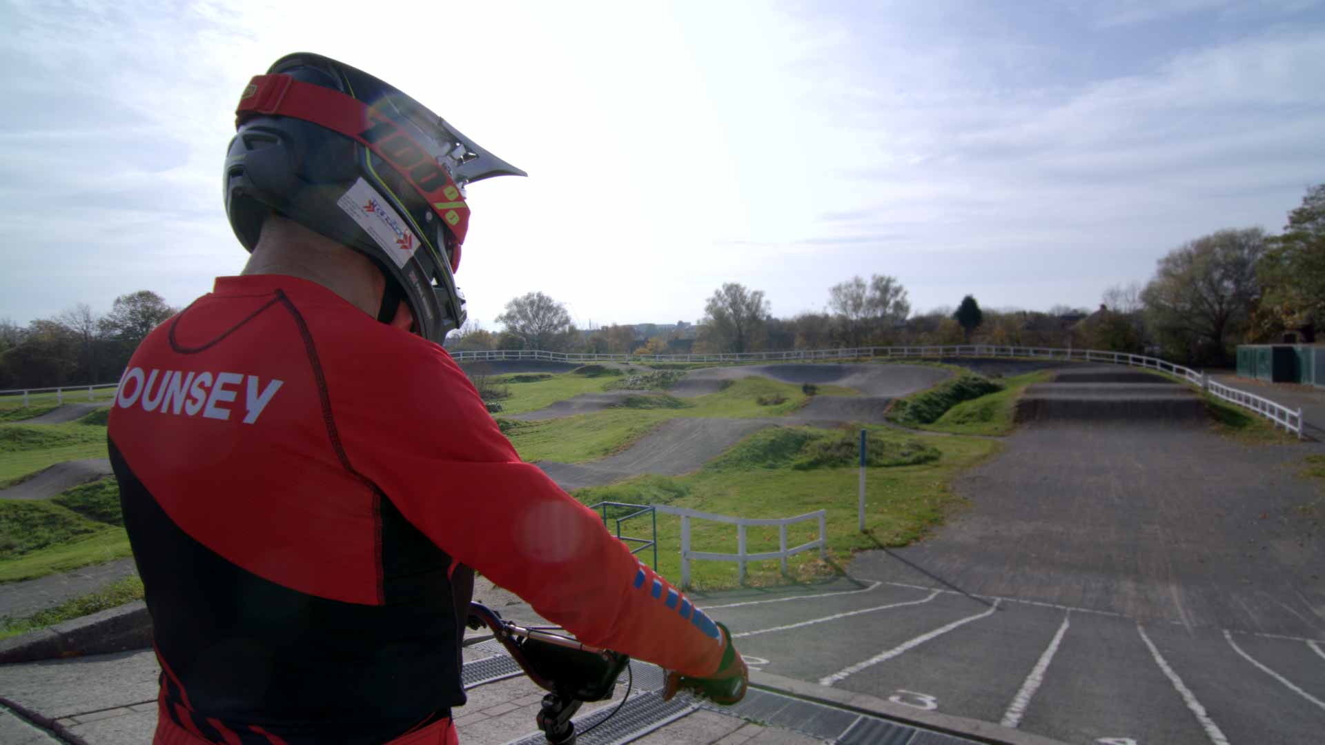 Paul Mounsey sat on his BMX at the start of a race track in full race gear.