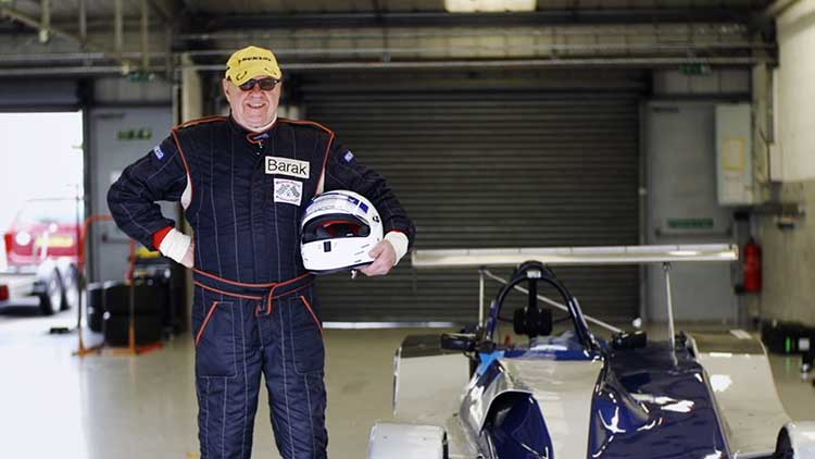 philip standing by a race car holding a helmet