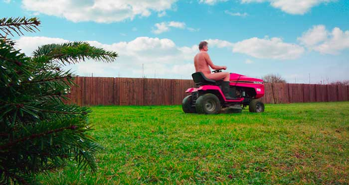 Richard driving a sit on lawn mower naked